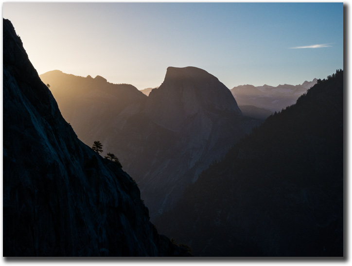 The sun rising over the Sierra Nevada behind Half Dome